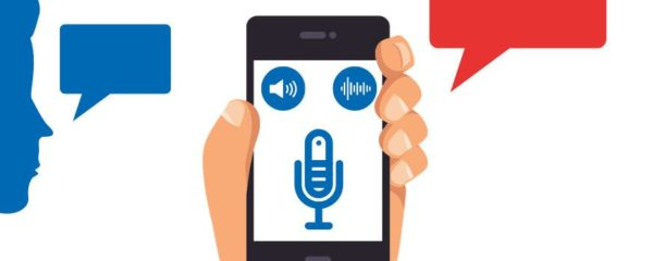 A smartphone showing the symbols of a microphone, a loudspeaker and a voice recognition software. On the left hand a speech bubble out of face silhouette, on the right side a speech bubble from the smartphone app. Symbolizing increased patient compliance for patient diaries for telemonitoring through speech recognition.